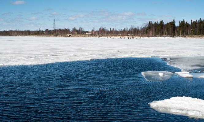 Eisfischer sitzen und liegen auf dem ufernahen Eis