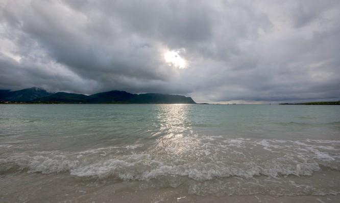 Sonne und Berg über türkisfarbenem Meer
