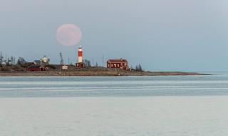21:26: Rosa Mond über dem Leuchtturm